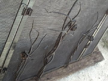 close up of wrought iron roses on fireplace screen