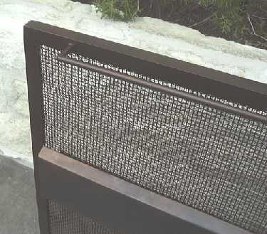 Close up of contemporary fire screen showing handle and angled edge of center band