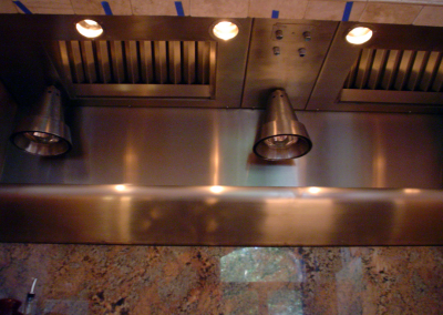 Custom stainless steel insert with hanging heat lamps and warming shelf. Randomly brushed stainless steel.